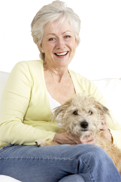 'A lady sitting down and smiling at the camera, cuddling her cute dog on her lap